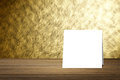 White card put on wooden desk or wooden floor on blurred abstract gold wall texture background.use for present your product.