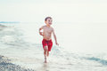 White Caucasian one young little boy in red swim shorts running on beach by water Royalty Free Stock Photo