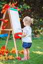 White Caucasian toddler child kid girl standing outside in summer autumn park drawing on easel with markers Royalty Free Stock Photo