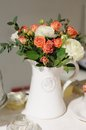 White ceramic jug full of flowers on a table Royalty Free Stock Image