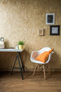 White chair with orange cushion in wooden interior Stock Image
