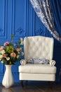 Blanco sillas de flores en azul pared