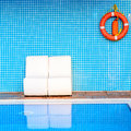 The life buoy is hanged on brick wall background nearby the swim