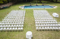 White chairs and pool outdoors dozens of positioned on grass lawn with swimming for private wedding occasion Royalty Free Stock Image