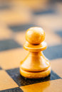 White chess pawn standing on chessboard single old wooden vintage Royalty Free Stock Photos