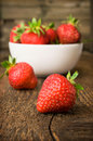 White china bowl filled with succulent fresh ripe red strawberries on an old wooden textured table top Stock Photos