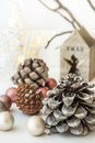 White Christmas decoration composition, big pine cones, scattered baubles, shiny star, wooden candle holder, dry tree branches in Royalty Free Stock Photo