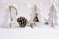 White Christmas decoration in scandinavian style with wood fir trees and pine cones, bokeh lights in the background Royalty Free Stock Photo