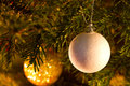 White christmas globe hanging from a branch of pine ball in tree with background lights Royalty Free Stock Photo