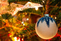 White christmas globe hanging from a branch of pine ball in tree with background lights Stock Photography