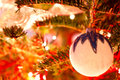 White christmas globe hanging from a branch of pine ball in tree with background lights Royalty Free Stock Image