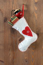 White christmas stocking on an old door filled with traditional gifts and toys hanging by a rusty nail in Stock Photo