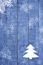 White Christmas tree made from felt on wooden, blue background. Snow flaks image. Christmas tree ornament, craft. Royalty Free Stock Photo