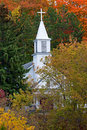 White church steeple in autumn a towers up into the trees maple city michigan st rita s catholic is a wonderful display Royalty Free Stock Photography