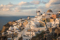 White city on a slope of a hill at sunset and pink clouds, Oia, Royalty Free Stock Photo