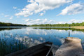 White clouds on the blue sky over blue lake with boats and board Royalty Free Stock Photo