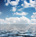 White clouds in the blue sky reflected in the water Royalty Free Stock Photo