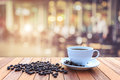 White coffee cup and coffee beans on wood table with blurred bac Royalty Free Stock Photo