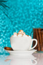 White coffee cup with cream against blue background and rolled cookie on reflective table Royalty Free Stock Photography