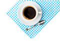 White coffee cup with saucer and spoon tableware on blue chequered napkin Royalty Free Stock Photo