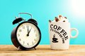 White coffee mug with cream and clock,on wooden table. Royalty Free Stock Photo