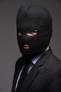 White collar crime portrait of businessman in black balaclava l looking at camera while on grey Stock Photo