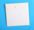 White compact disc envelope old and stained blank paper used to store a on a plain blue paper background with copy space Stock Photography