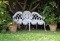 White cottage garden love seat photo of a pretty ornate iron with potted plants at side Stock Photography