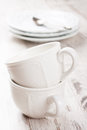White crockery for tea cups milk jug and teapot on vintage background selective focus Royalty Free Stock Image