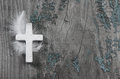 White cross with feather on an old rustic background. Royalty Free Stock Photo