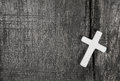 White cross on a grey wooden background. Royalty Free Stock Photo