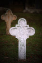 White cross old without inscription in dark grassy graveyard Royalty Free Stock Images