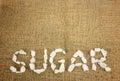 White crystalline sugar arrange as word sugar on brown hemp Royalty Free Stock Photos