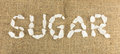 White crystalline sugar arrange as word sugar on brown hemp Stock Photography