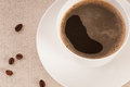 White cup with black coffee and beans on canvas Royalty Free Stock Images