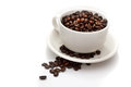 White cup with coffee beans in and some overflowed Royalty Free Stock Photos