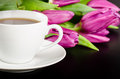 White cup of coffee with bunch of purple tulips on dark backgrou Royalty Free Stock Photography