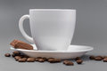 White cup of coffee with candy on a gray background