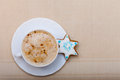 White cup coffee and christmas gingerbread cake star of hot beverage drink cappuccino latte homemade with icing blue decoration Stock Images