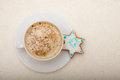 White cup coffee and christmas gingerbread cake star of hot beverage drink cappuccino latte homemade with icing blue decoration Stock Image