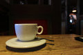 White cup in a dark cafe teaspoon and saucer on wooden table the Royalty Free Stock Image