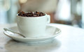 White cup filled with roasted coffee beans Royalty Free Stock Photo