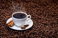 White cup of hot coffee on coffee beans Stock Images