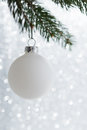 White decorative ball on the xmas tree on glitter bokeh background. Merry christmas card. Royalty Free Stock Photo