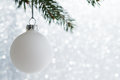 White decorative ball on the xmas tree on glitter bokeh background. Merry christmas card. Royalty Free Stock Photo