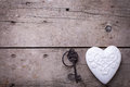 White  decorative  heart and vintage key on aged wooden backgrou Royalty Free Stock Photo