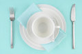 White dishes on aqua tablecloth Stock Photos