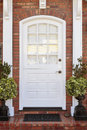 White door to classic brownstone home is framed by detail a doormat and two plants Royalty Free Stock Photography