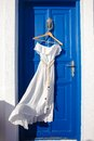 White dress on blue door in greek house Royalty Free Stock Photo