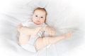 White dressed baby pretty lies on bed Royalty Free Stock Images